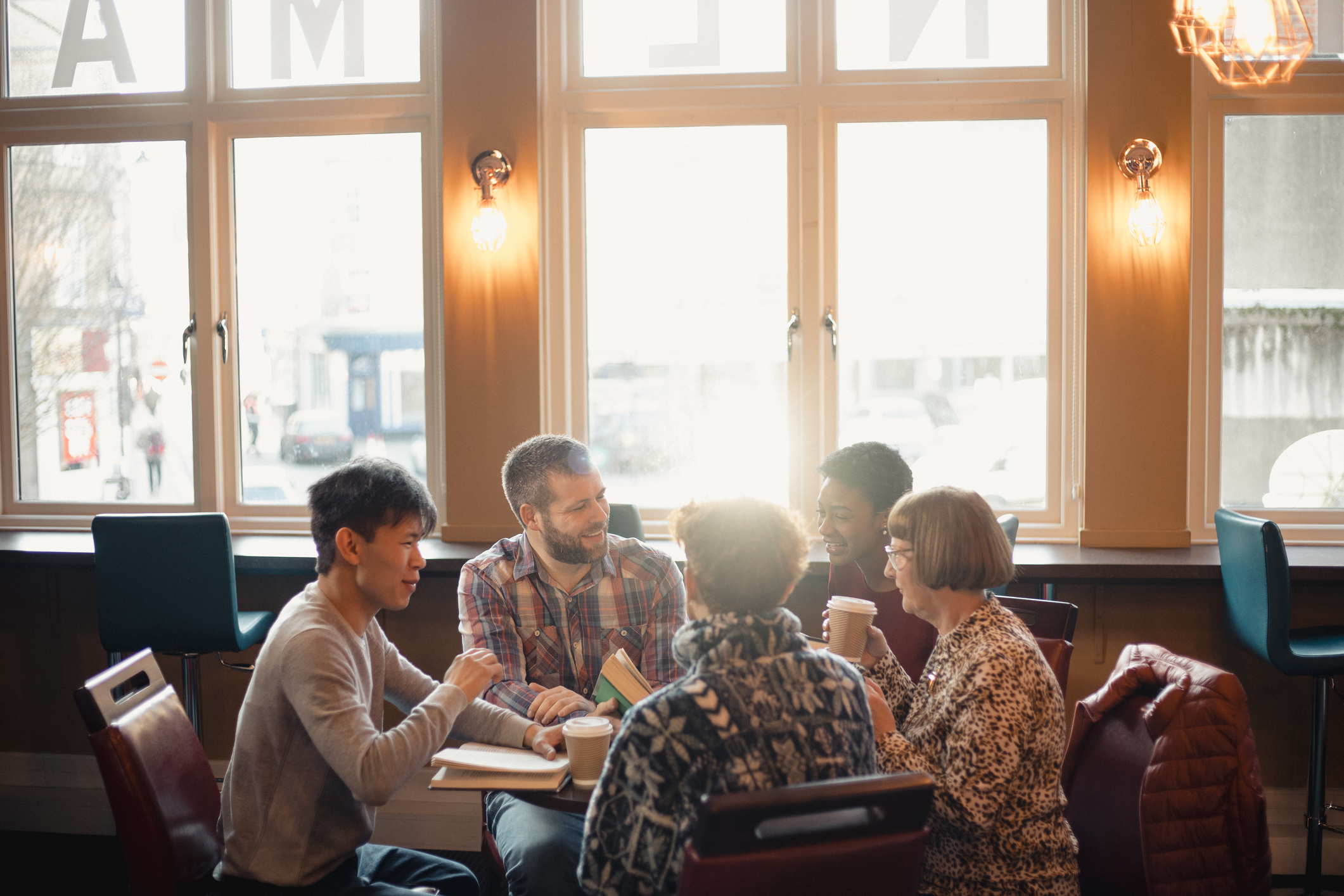 Small group of people with a mixed age range sitting around a table in a cafe. They are talking during a book club.